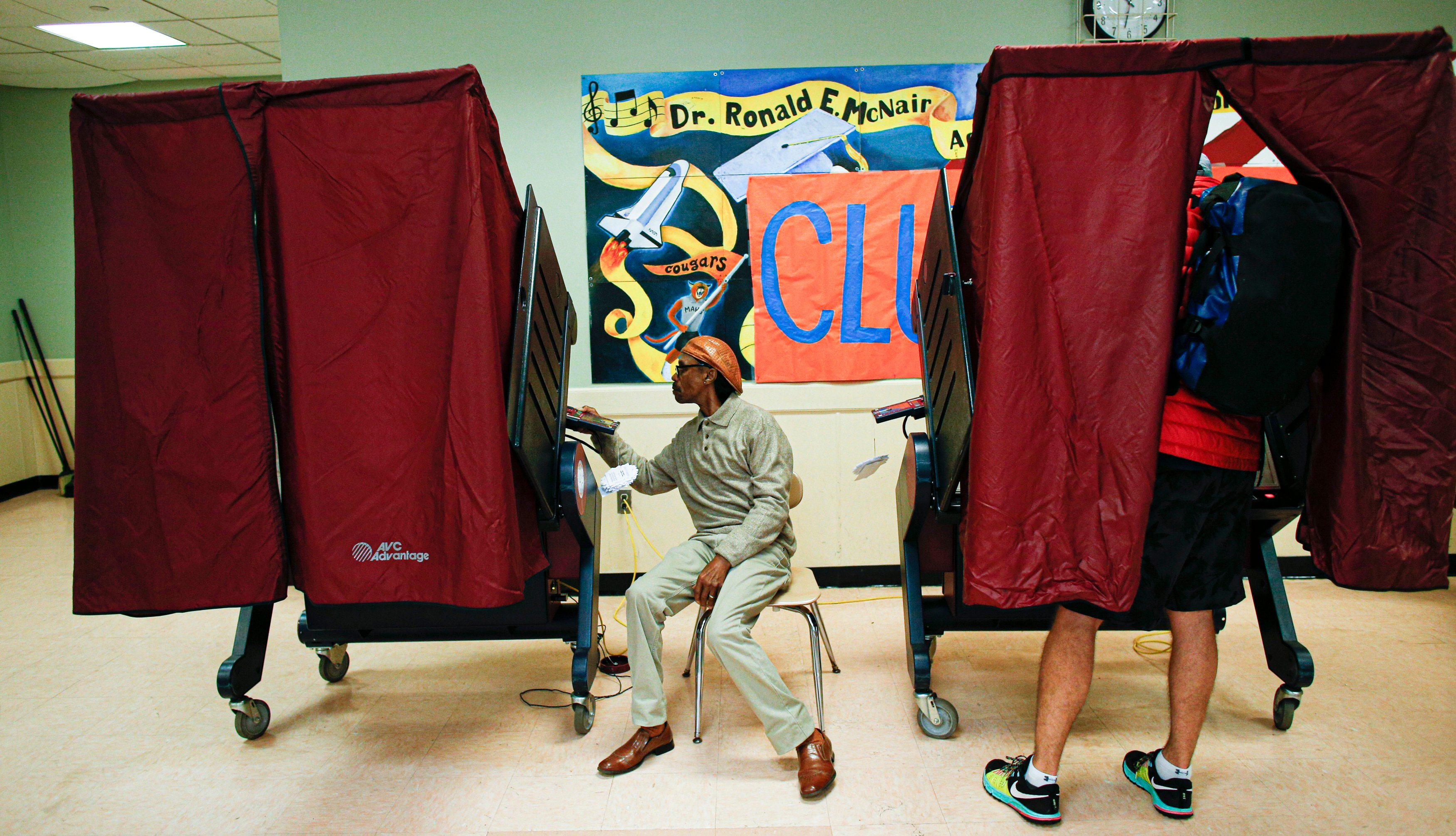 a man votes in a red-curtained polling booth at a school