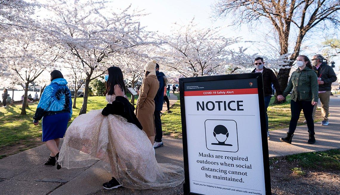 People wearing masks walking through a park