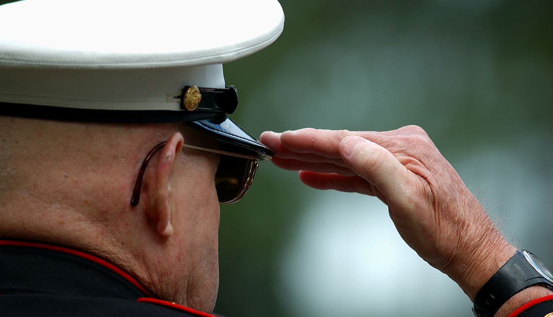 Un veterano con uniforme de la marina de EEUU saluda