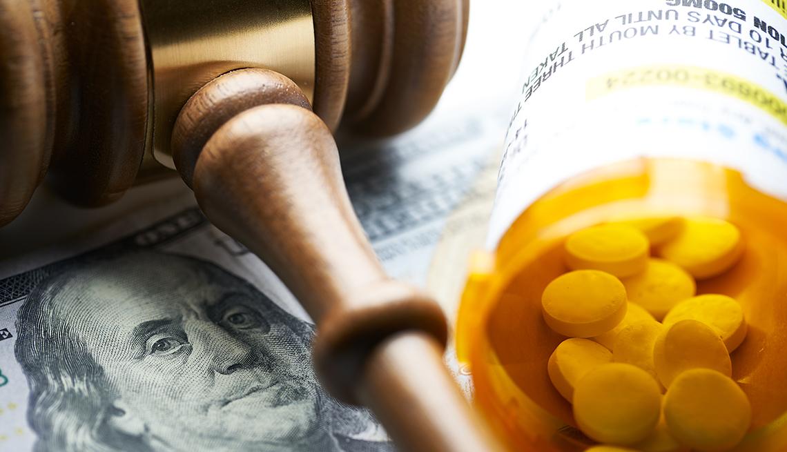 A gavel on money next to a prescription bottle with pills