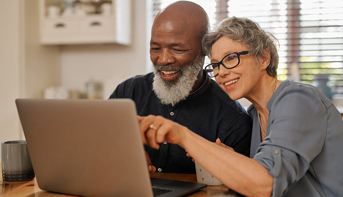 A man and a woman are looking at a computer screen