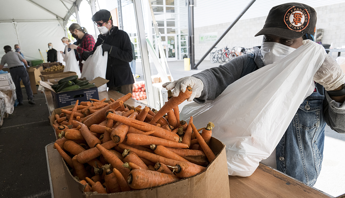 A woman is putting a carrot into a bag