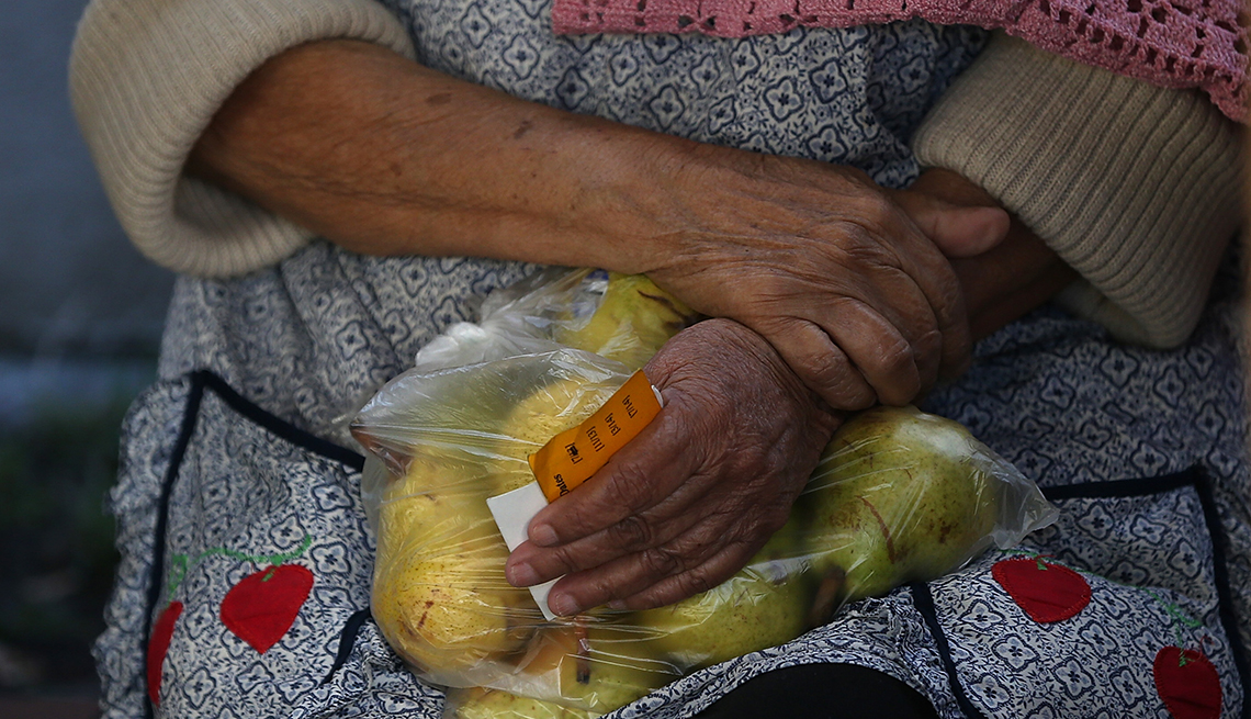 A woman is holding a bag of pears
