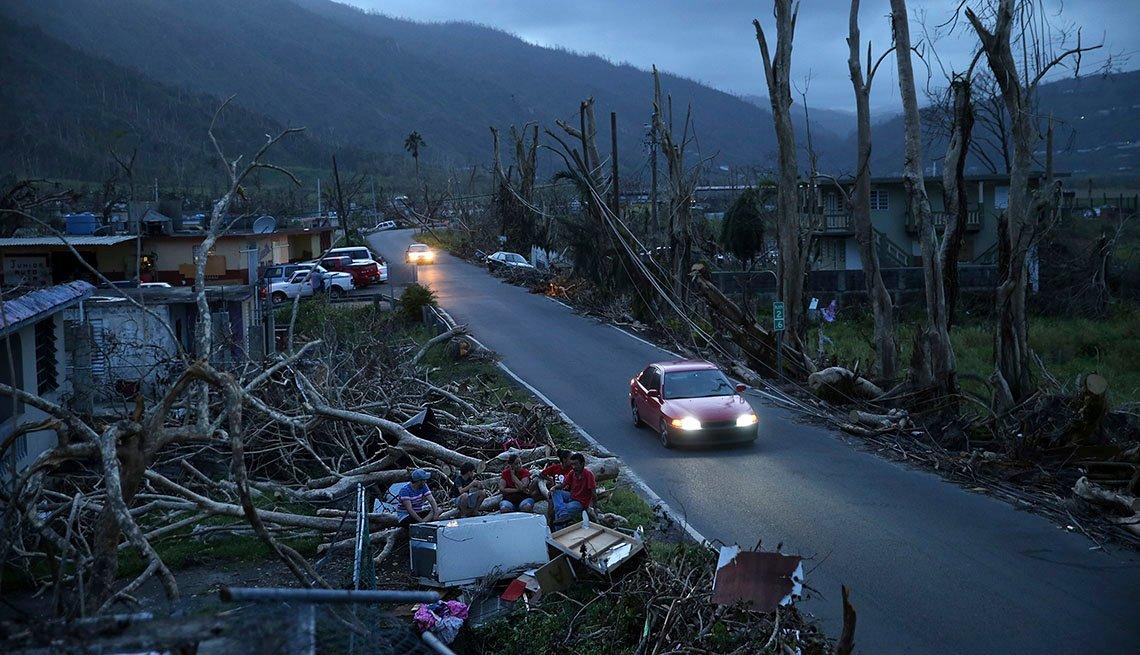 Vecinos están sentados en sofás donde antes estaban sus casas, que quedaron destruidas por el huracán María en Yabucoa, Puerto Rico.