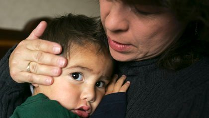 Woman embraces a  child who may be sent back to Mexico
