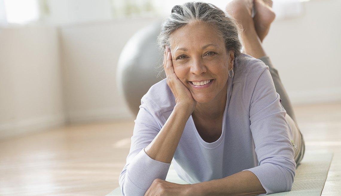 Mujer acostada sobre una estera de yoga