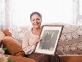 Mujer hispana de mediana edad sosteniendo una foto antigua de una pareja