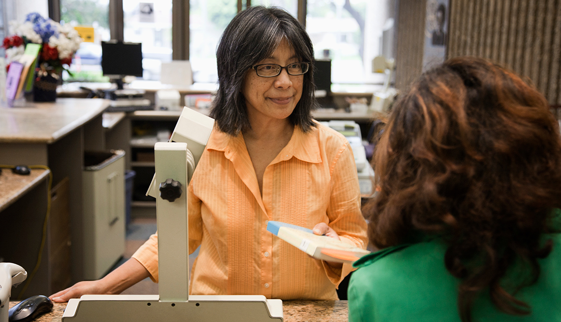 Librarian, checking out books, library, AARP, Public Policy Institute, Future of Work @ 50 +