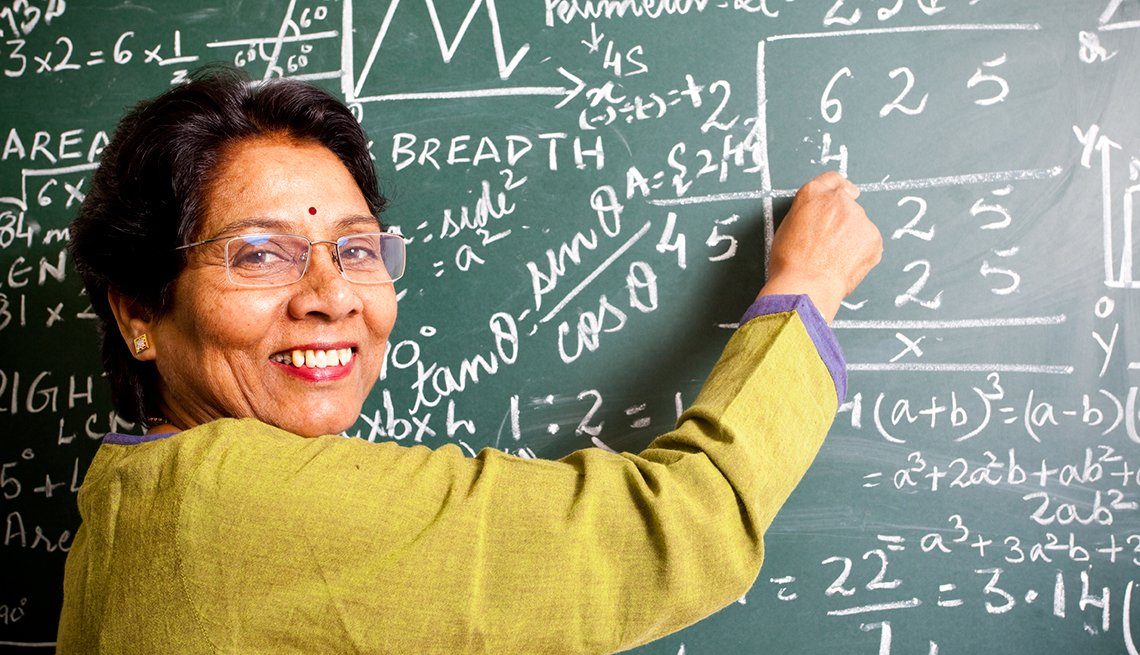 Female teacher, smiling, blackboard, AARP, Public Policy Institute, Future of Work @ 50 +