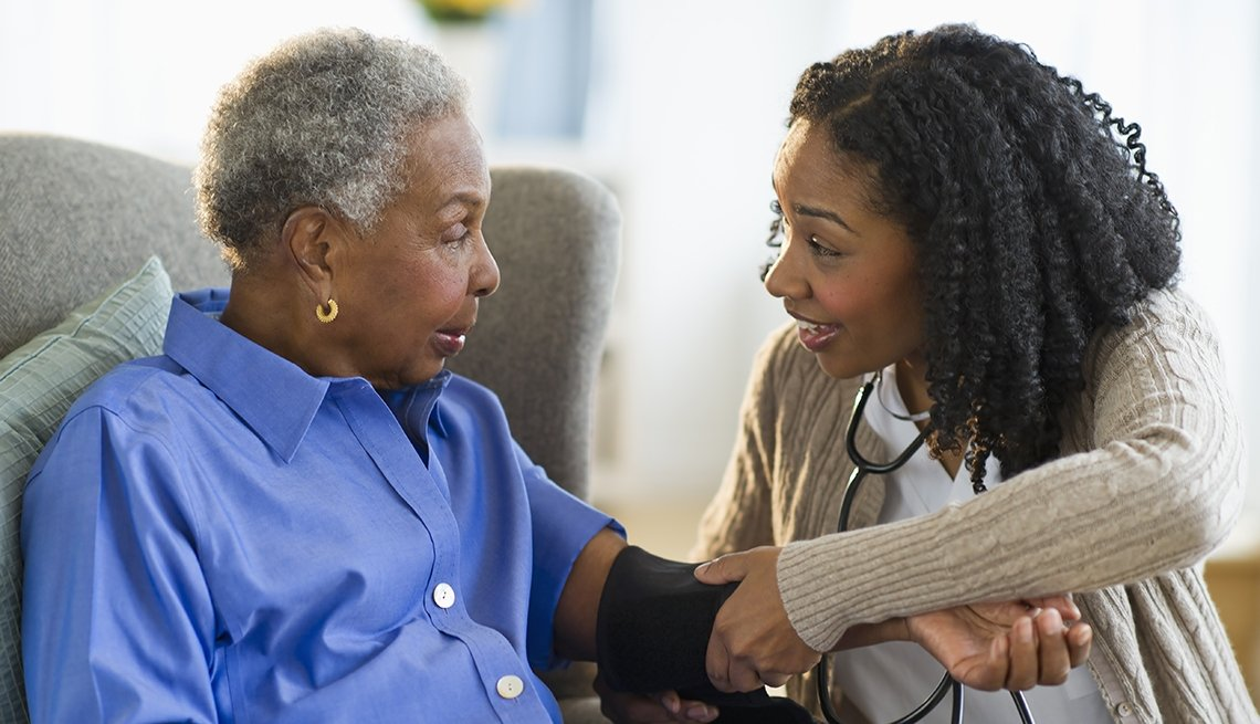 Elderly African American Patient Sits In A Chair As A Nurse Checks Her Blood Pressure, AARP PPI