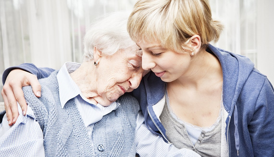 An Elderly Woman, Comforted By A Younger Woman, AARP Public Policy Institute