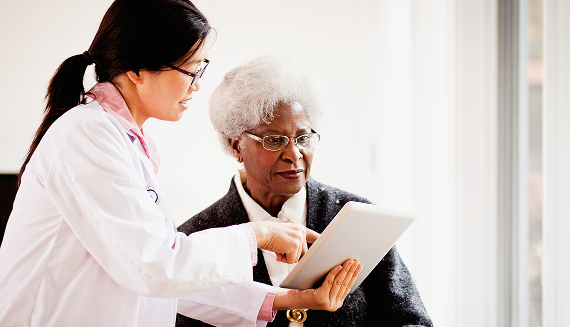 Asian doctor, mature African-American patient, digital tablet, meeting, Public Policy Institute, Issues, Health