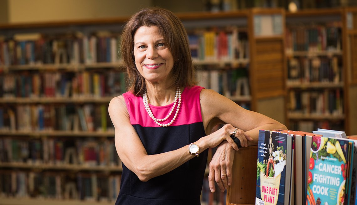 Sari Feldman leaning on a bookcase in one of the Cuyahoga County, Ohio libraries