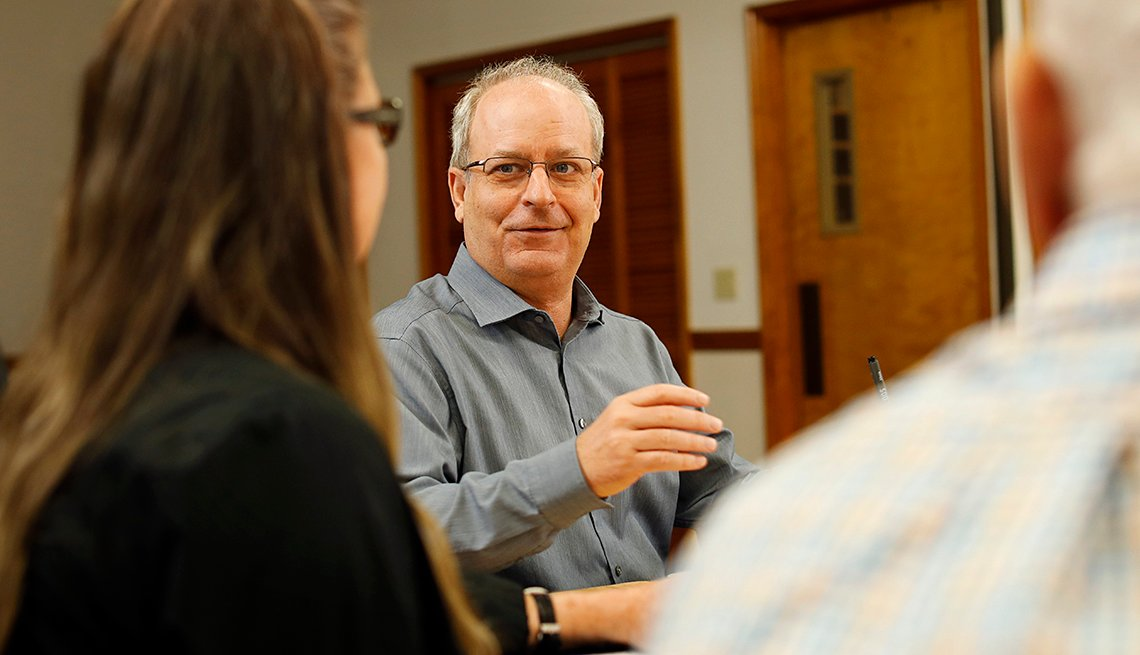 Scott Miller talks with coworkers during a meeting.