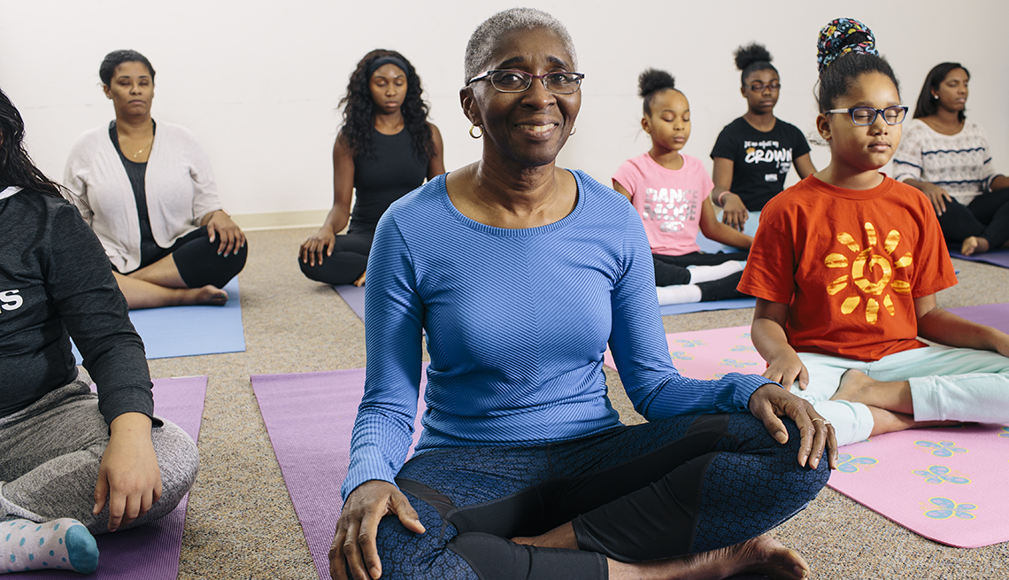 Dr. Shireen Lewis sitting on a yoga mat during a yoga class