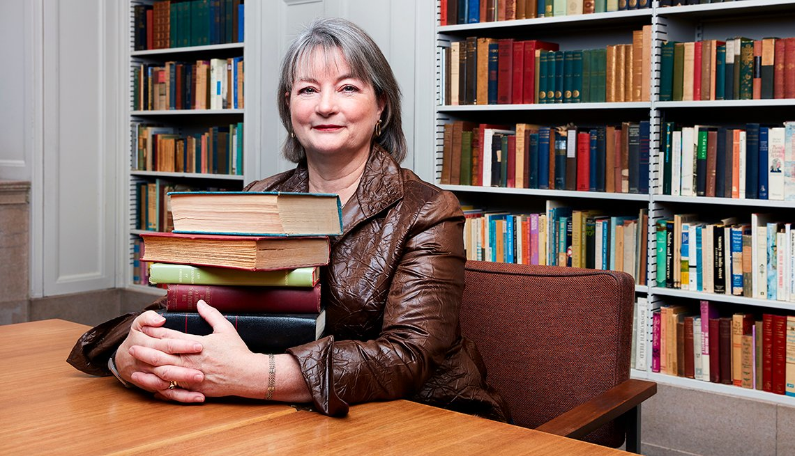 Siobhan Reardon sitting at table holding stack of books.