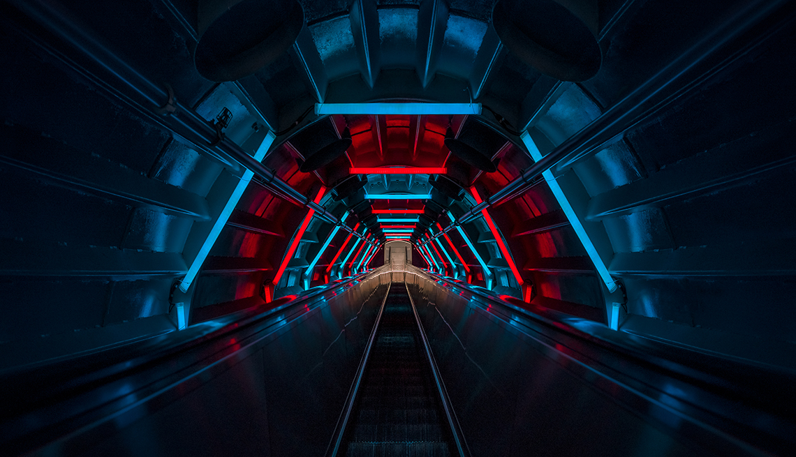 Long escalator inside a subway tunnel surrounded by red and blue lights
