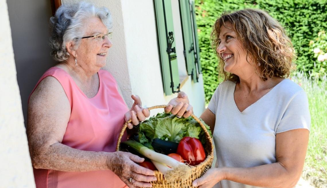 Cheerful woman delivering vegetable basket