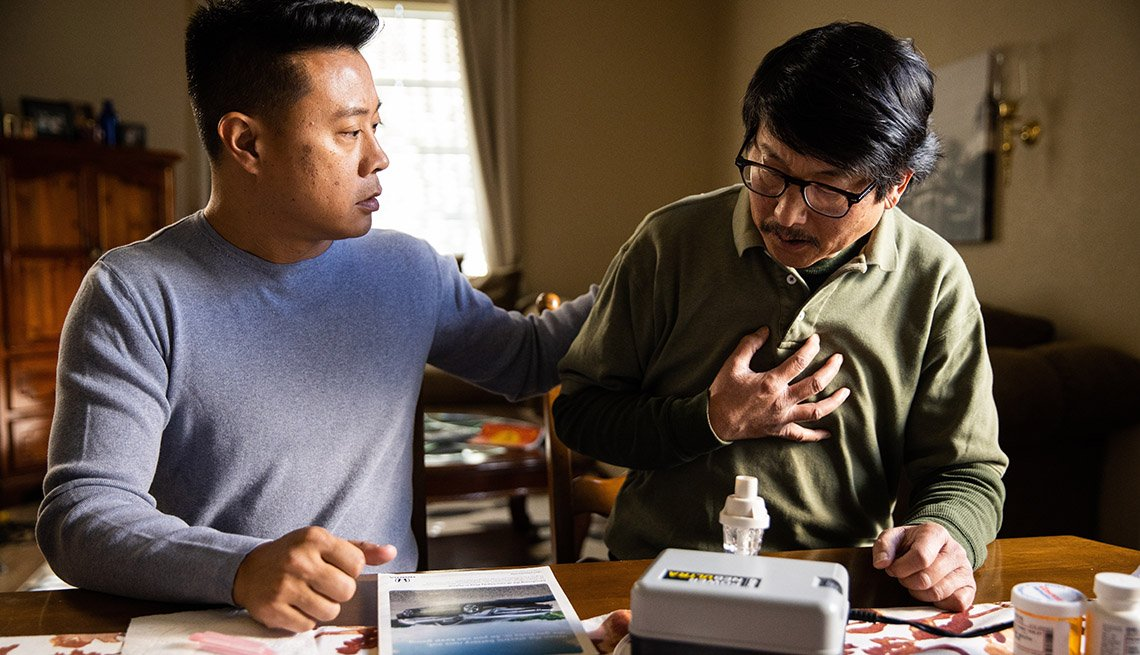 Son caregiving for his father with medical equipment
