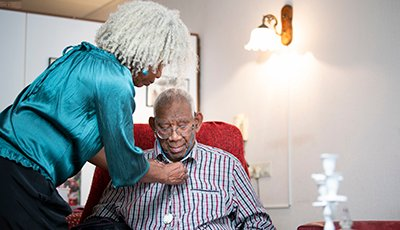 Woman giving informal care to a 91 year old man in a home