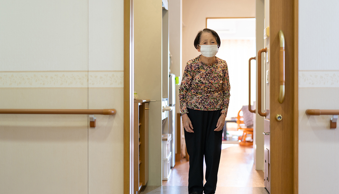 Older Asian woman in nursing home wearing a mask