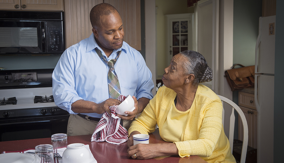 A caregiver drying dishes for his mother while she sits at the kitchen table