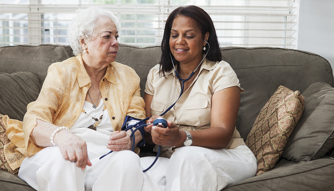 A woman getting her blood pressure taken at home by her caregiver