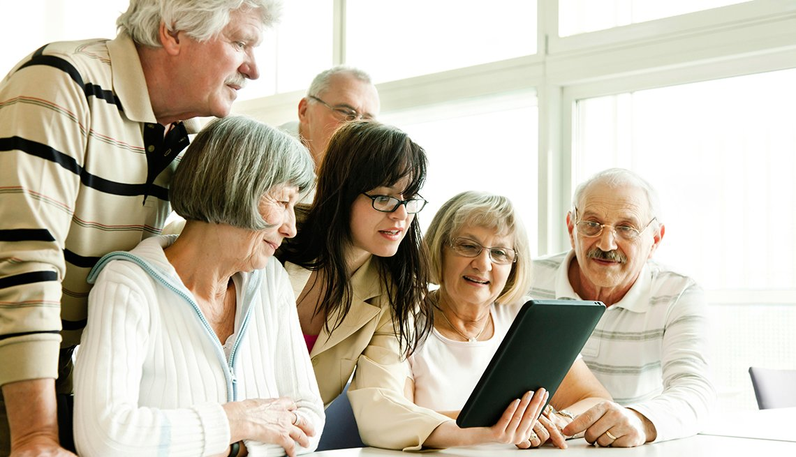 group of seniors at lecture examine tablet pc
