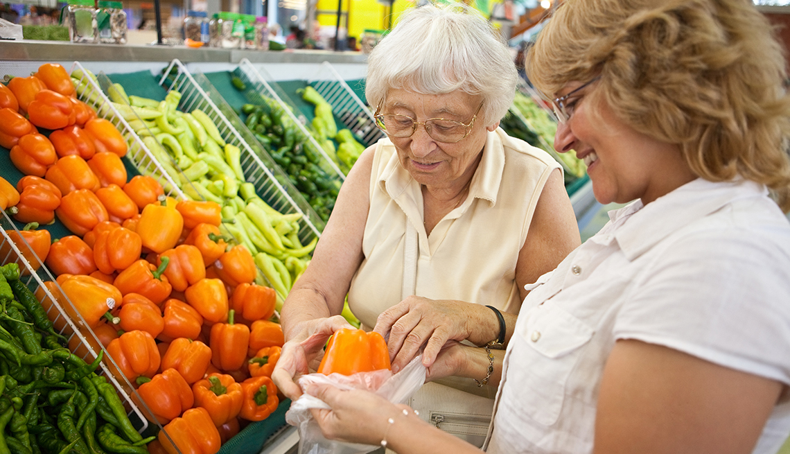 A woman and her adult daughter grocery shopping in the produce isle