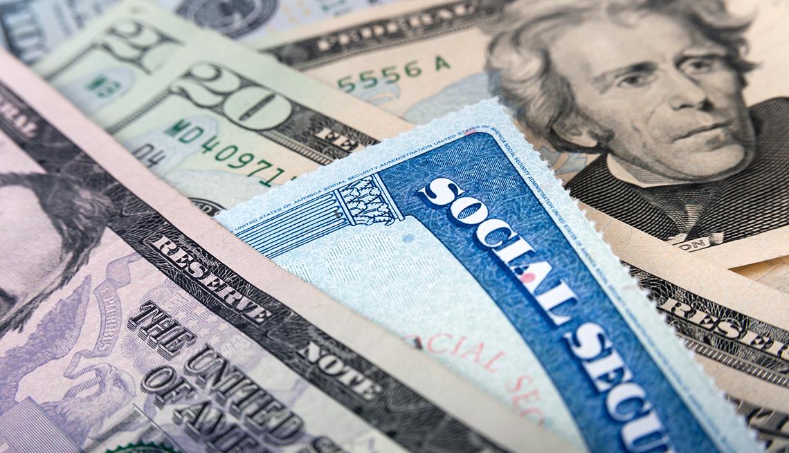 A pile of twenty dollar bills with a social security card on top