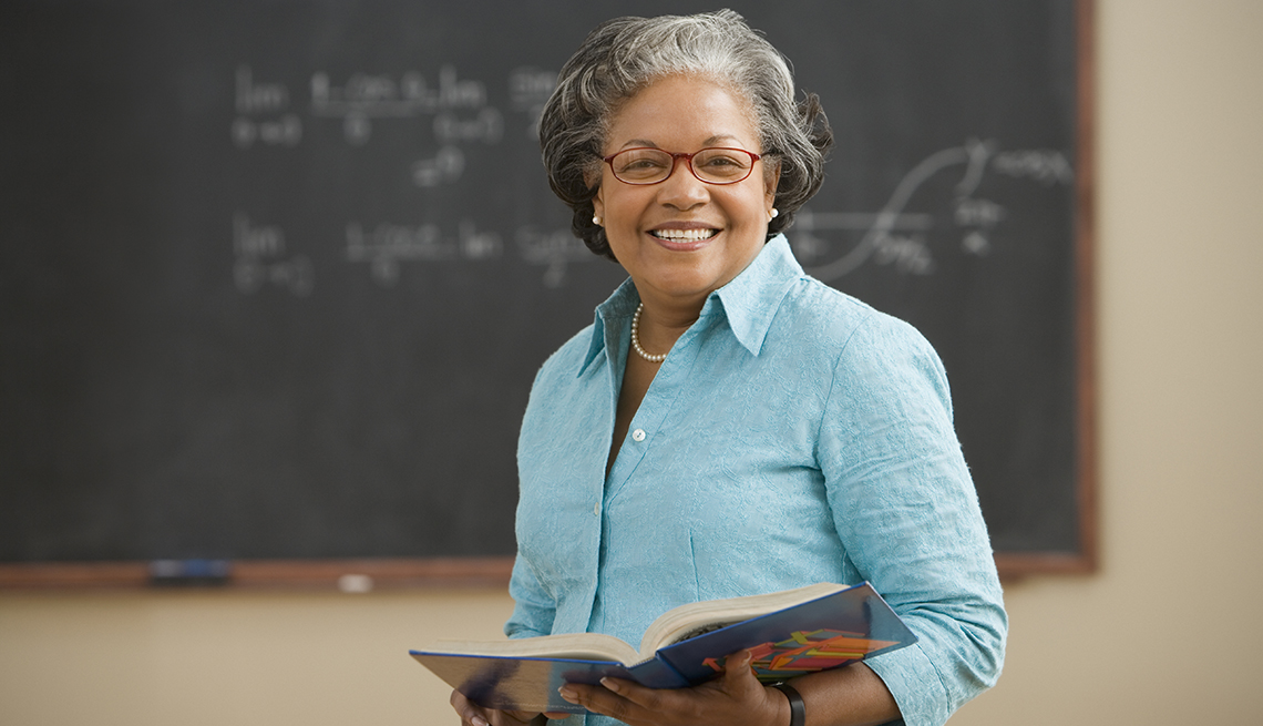 A female teacher standing in front of a chalkboard holding a book