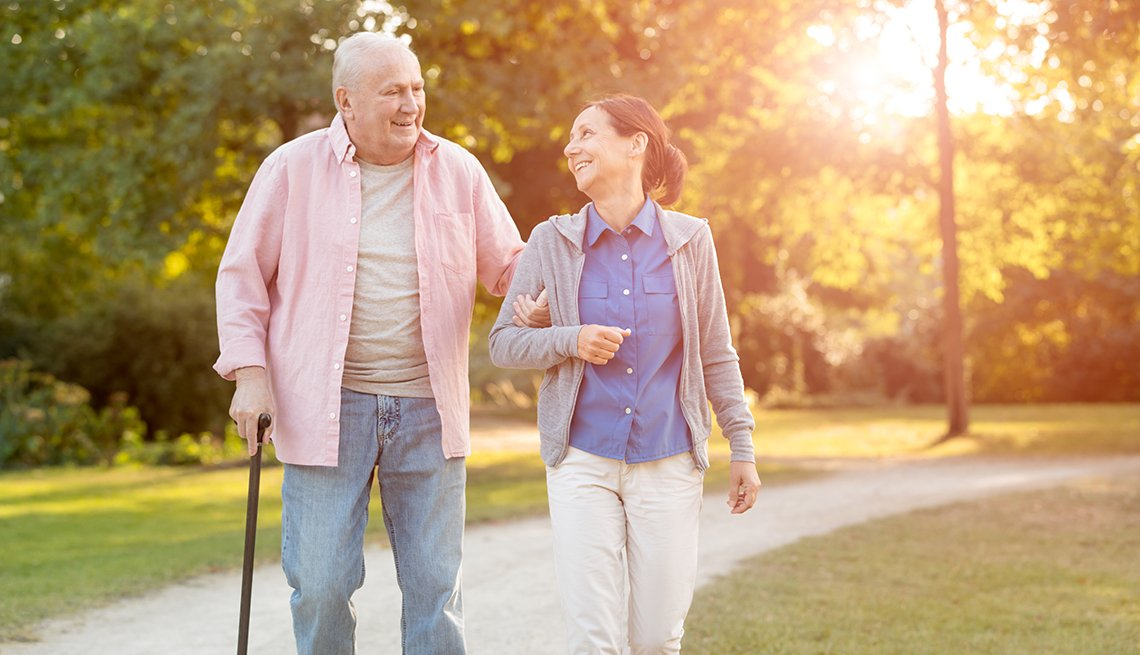 A man with a cane and his caregiver walking in a park