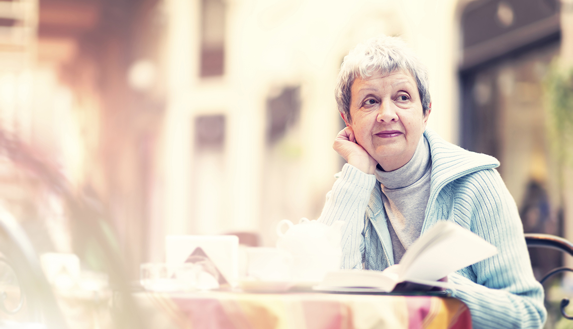 Woman with book sitting in a restaurant looking off into the distance
