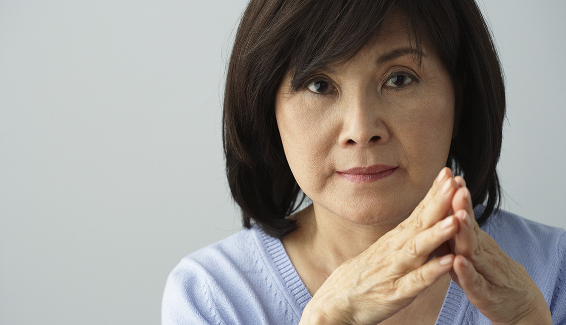 A woman with her hands together, looking worried