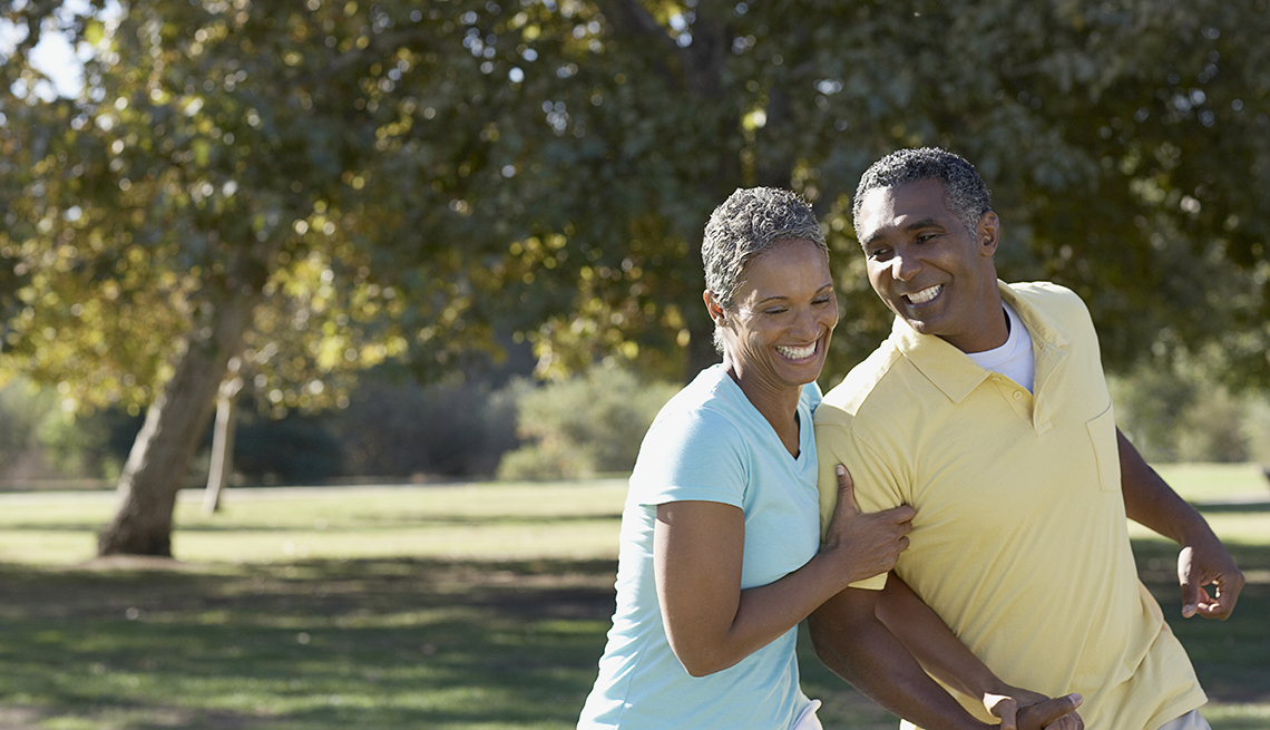 Happy retired couple walking in the park and laughing