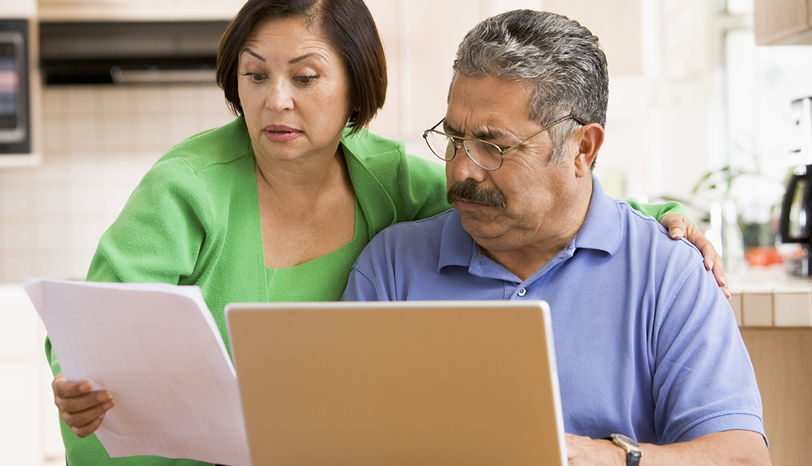 Couple looking at a computer and tax papers looking concerned