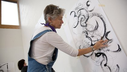A woman creates repetitive shapes on a piece of paper.