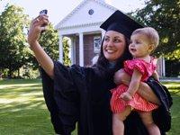 Mujer con su ajuar de graduada tomándose una foto con su hija