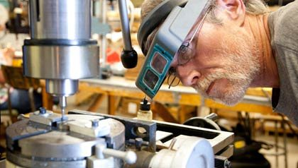 man with goggles - Glenn Cotter works at Vita needle factory, a company primarily composed of senior citizens