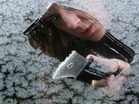 Woman scraping snow off window - cheap ideas for beating the winter blues