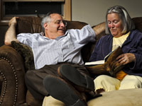 A couple enjoys the pleasure of reading out loud on the couch.