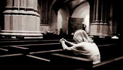 Mujer rezando en una iglesia