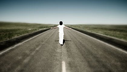 A man walks down a road with his arms outstretched toward the horizon.