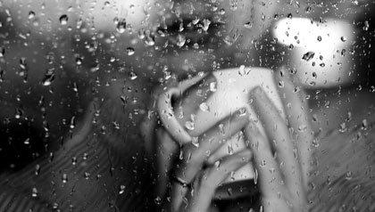 Woman caresses a coffee mug on a rainy day-heaven on earth