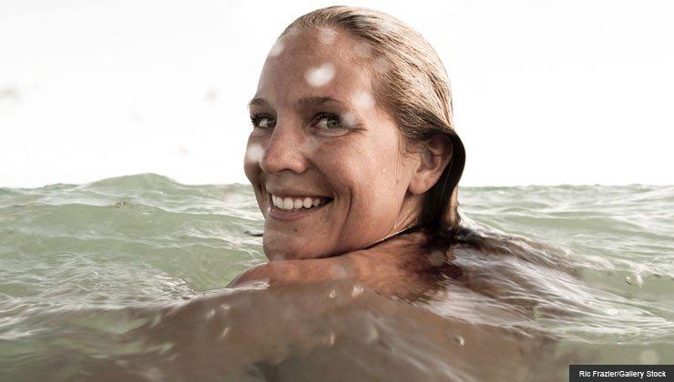 Woman swims in the open ocean water - heaven on earth