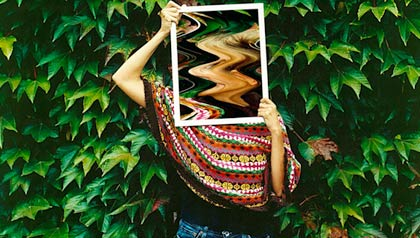 A woman with a mirror in front of her face.