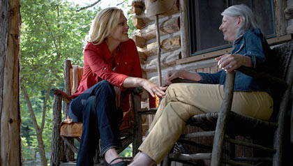 Two women speaking to each other on a country home porch.