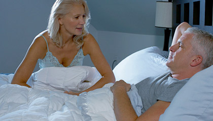 Husband and wife speaking to each other in bedroom.
