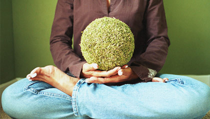 A woman holding a giant seed while meditating.