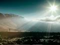 Un hombre solitario en un paisaje con un reflejo del sol - Cree usted en milagros?
